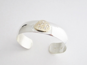 Sterling silver cuff bracelet with 14kt yellow gold free form plate and diamonds